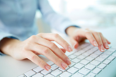 Audio transcription services worker typing on keyboard